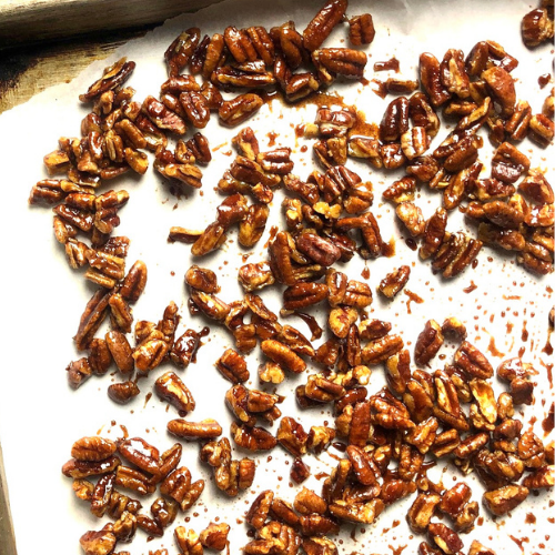 Candied pecans on parchment paper and baking sheet